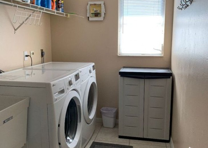Laundry Room with Front Loading LG Washer and Dryer and Utility Sink