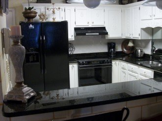 Granite counter tops and flat top electric stove. Side by side refrigerator