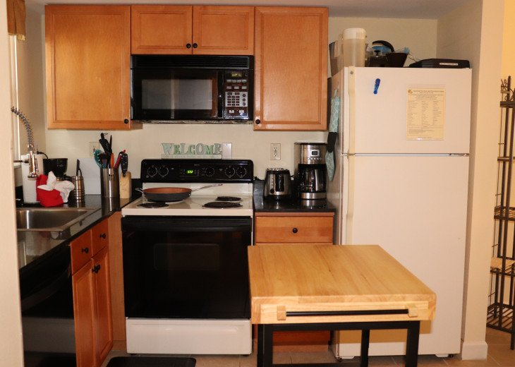 Fully stocked kitchen with copper pan, toaster, coffee pot, blender, and mixer