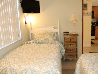 2nd bedroom with 2 twin beds, 2 small dressers, and tv