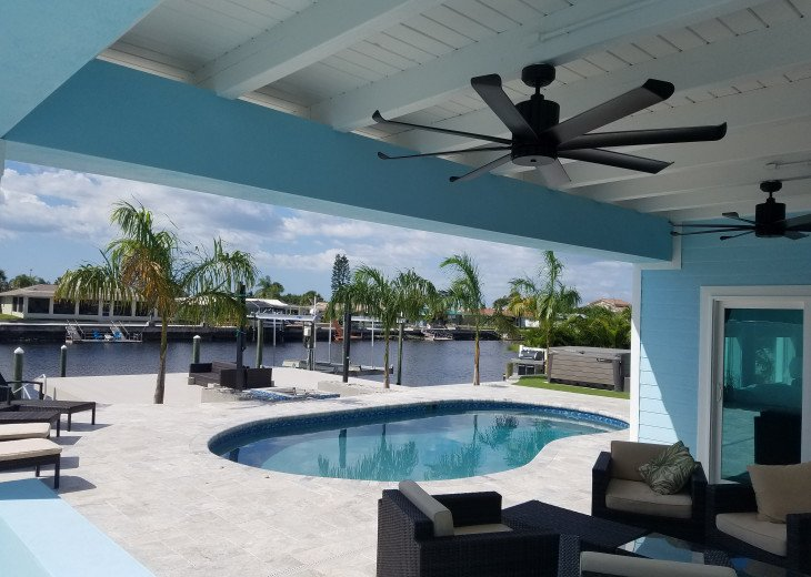 """Covered lanai with 65"""" TV, fans, and seating"""