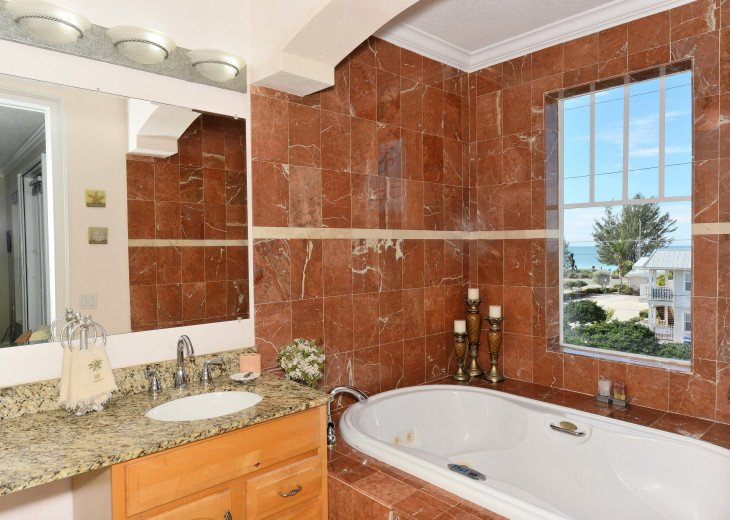 MASTER SUITE BATH WITH GULF VIEW, AND MARBLE, GRANITE, AND TRAVERTINE.