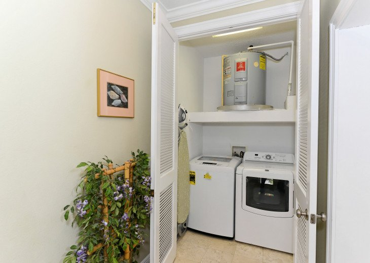 HIGH-EFFICIENCY WASHER AND DRYER, IRON, AND IRONING BOARD ON THE THIRD LEVEL.