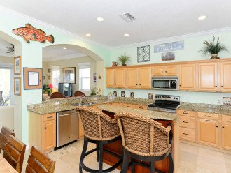 FULLY EQUIPPED KITCHEN WITH TOP-SHELF SMALL APPLIANCES.