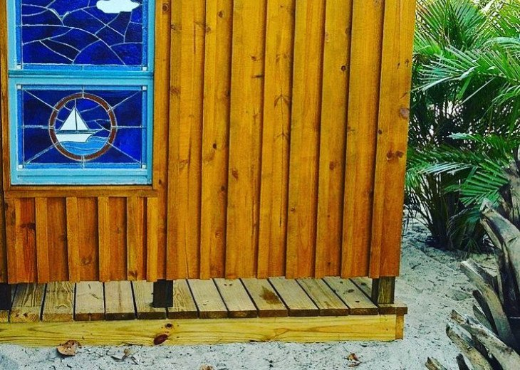 Beautiful extra large outdoor shower with vintage stained glass of sailboat