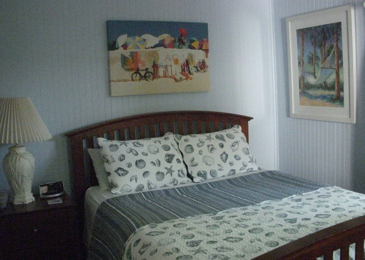 Nautical bedroom has a queen size bed, bedside tables, chest and closet