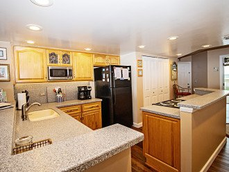 Open Plan Kitchen with Hickory Cabinets & Corian Counters