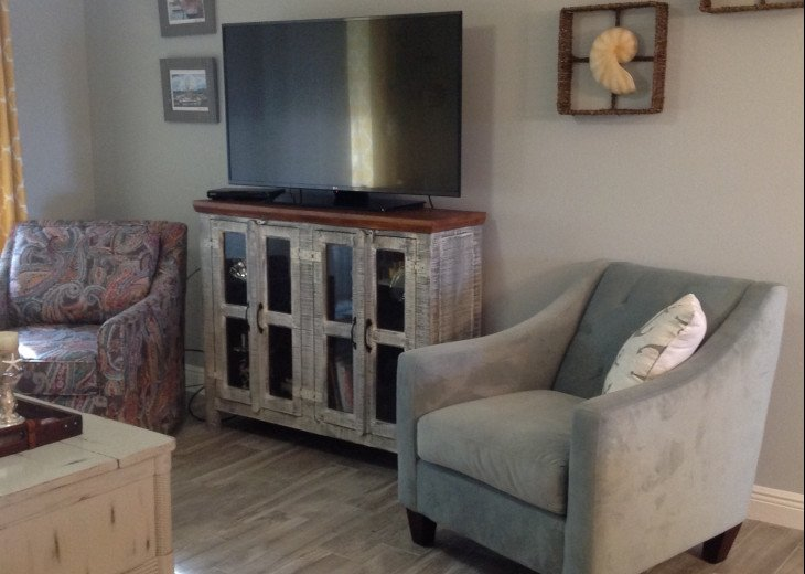 Living Room with very comfortable seats, Flat Screen TV, colors and books in cab