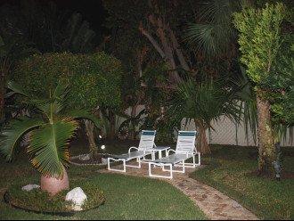Landscape lit tropical patio with lounges