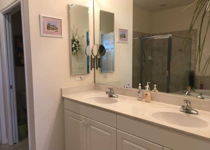 Master bath with double sinks, walk-in closet, tub and separate room for comode