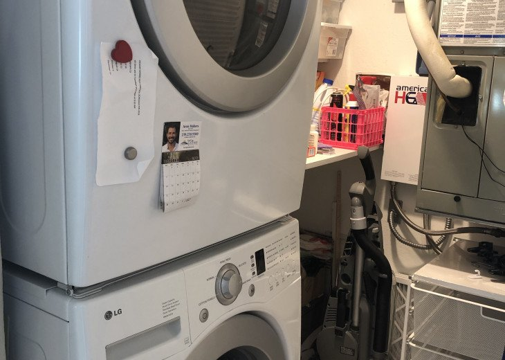 Laundry room with full size washer dryer and plenty of cleaning supplies.