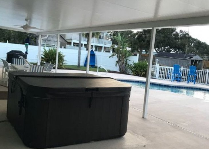 52 foot long covered patio with hot tub and patio furniture.