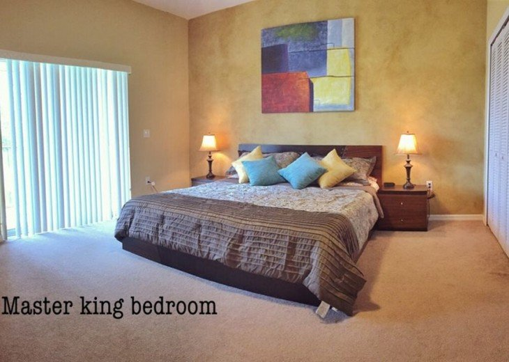 Master bedroom with king bed and inside bathroom.