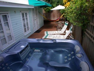 Wraparound back deck with Sundance spa, lounge chairs, dining table, hammock