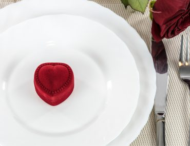 romantic restaurant with plate, rose, and ring
